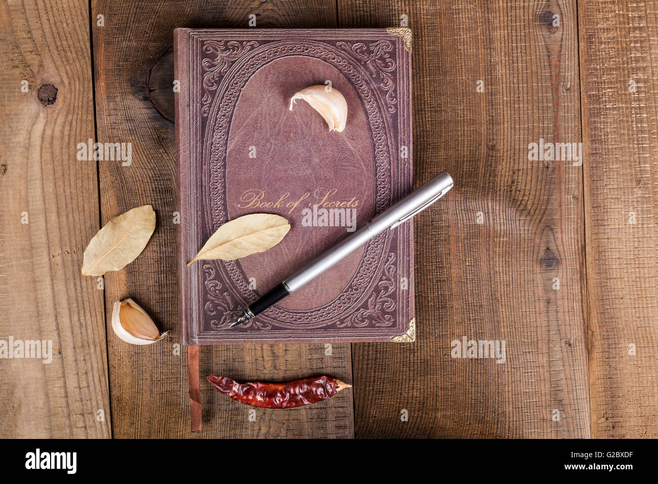 Book of Secrets brown closed cookbook on old wood background with spices - Stock Image