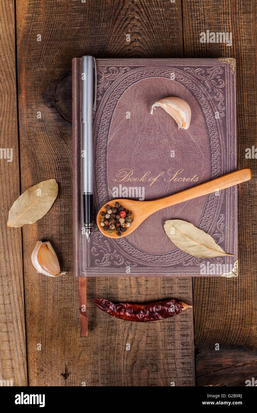 Book of Secrets broen closed cookbook on old wood background with spices - Stock Image
