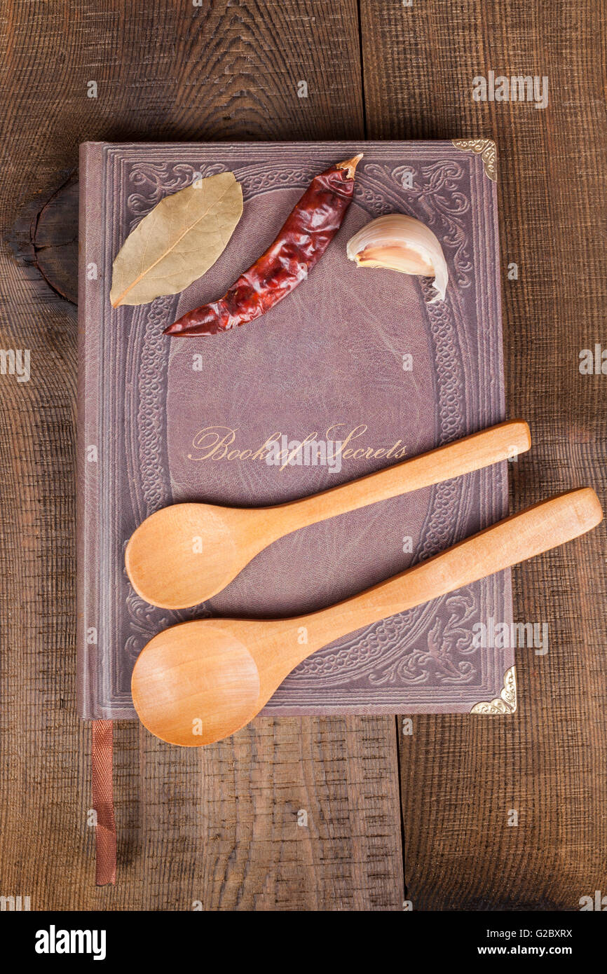 Book of Secrets brown closed cookbook on old wood background with spices and two  spoons - Stock Image