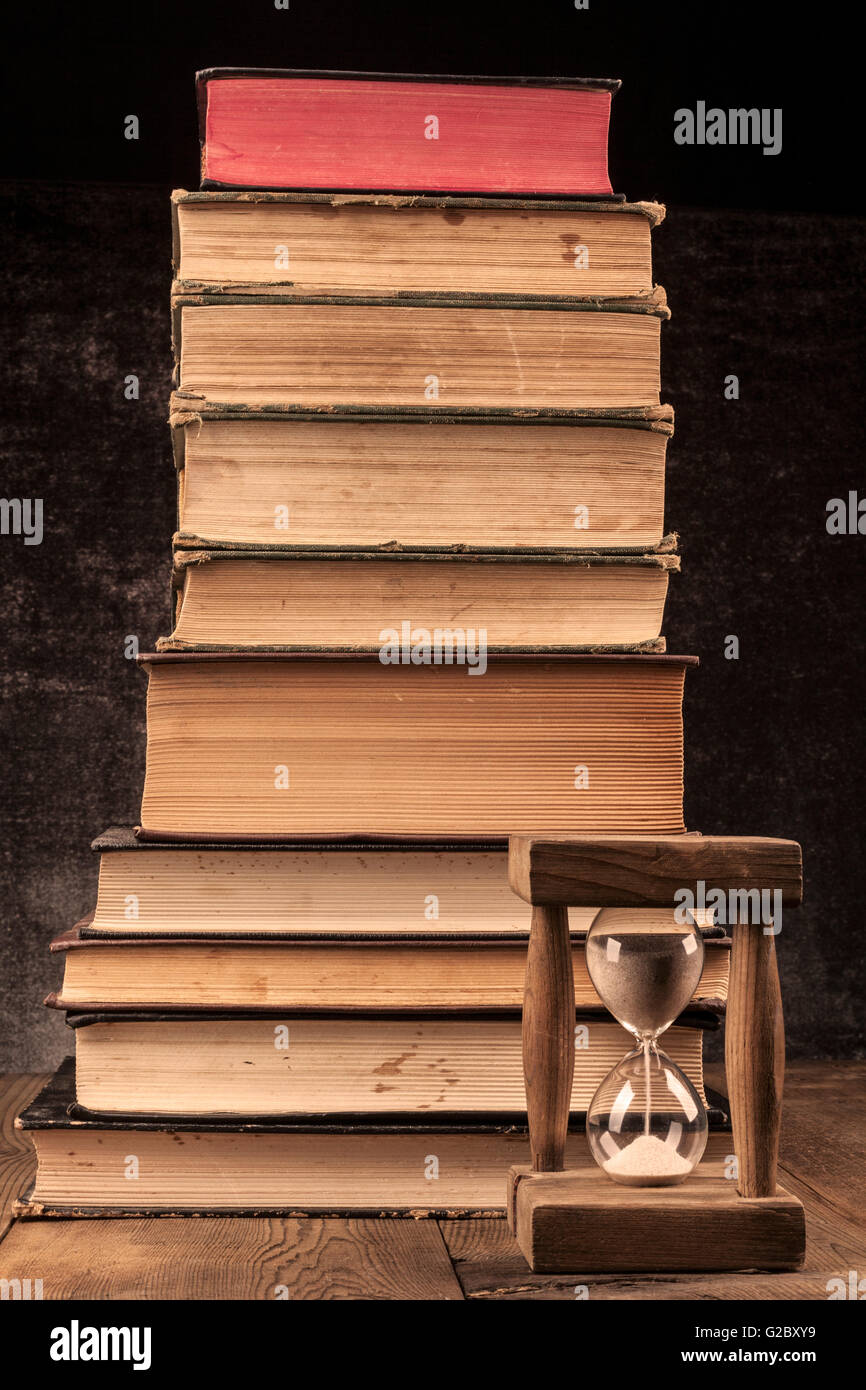Old Books Pile on Wood Table with Hourglass and Dark Background Stock Photo