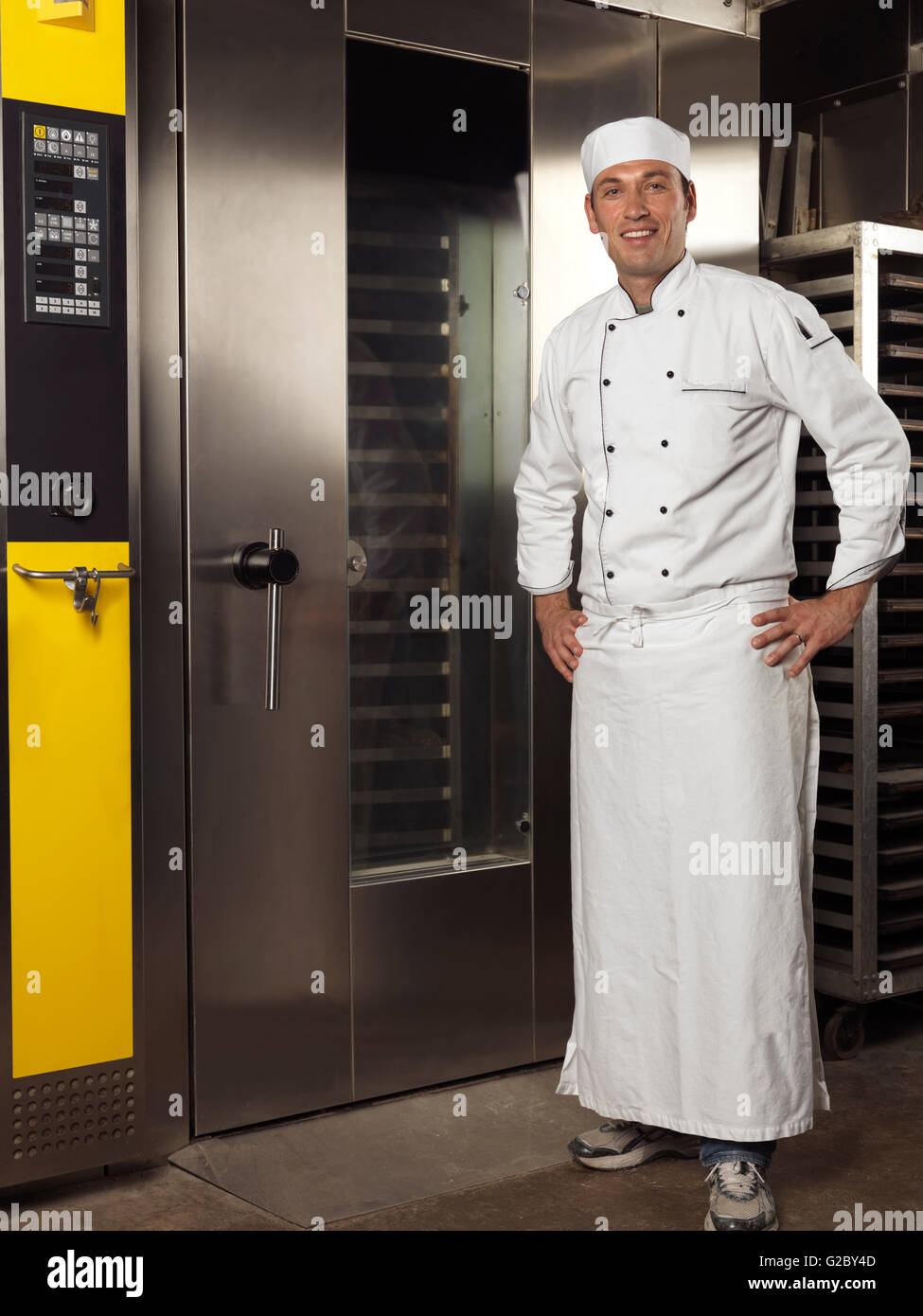 Smiling baker standing at a commercial bakery oven - Stock Image