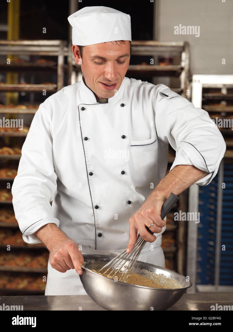 Baker whisking batter in a bowl - Stock Image
