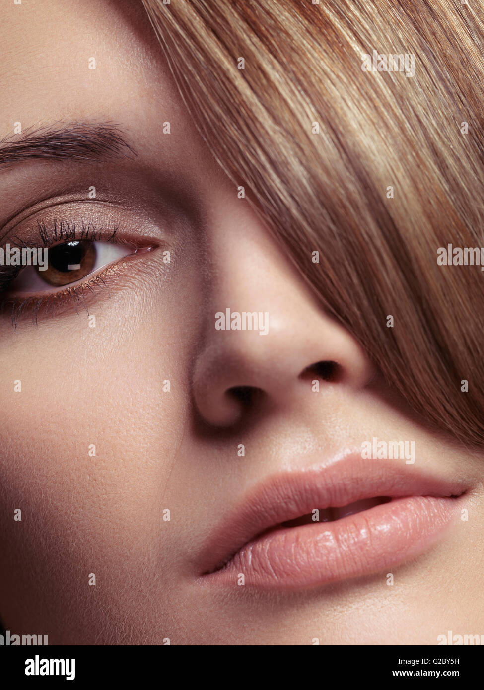 Portrait of a woman, bangs covering one eye - Stock Image