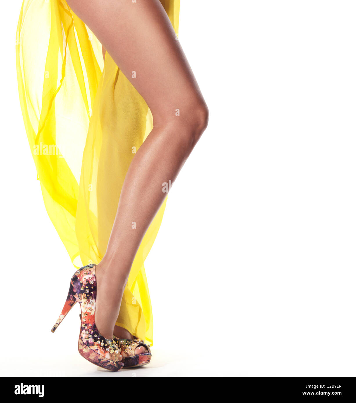 Legs of a woman wearing a yellow summer dress and high heels - Stock Image