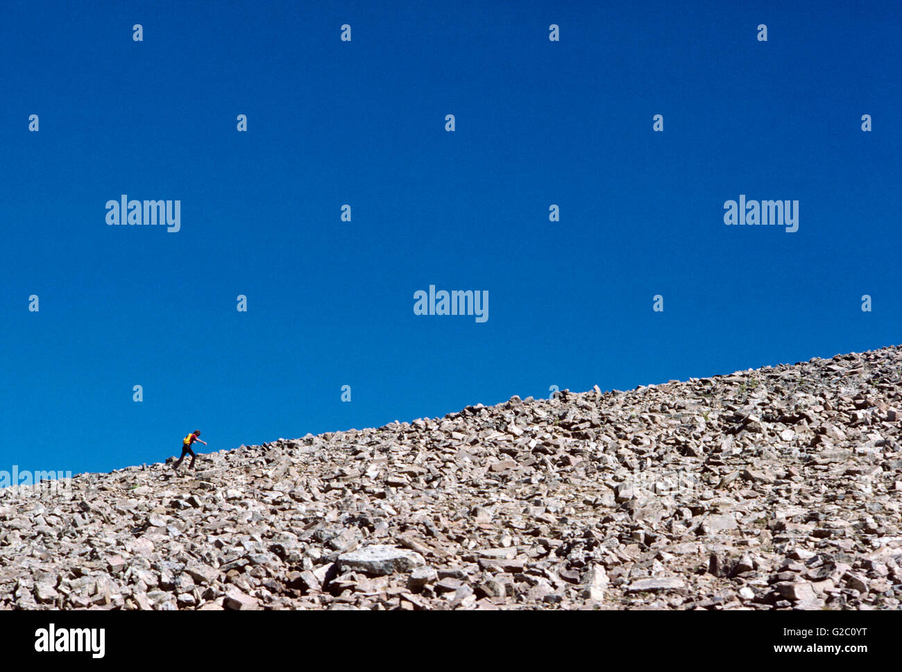 Lone mountain climber on scree slope; Uintah Mountains; Utah; USA - Stock Image
