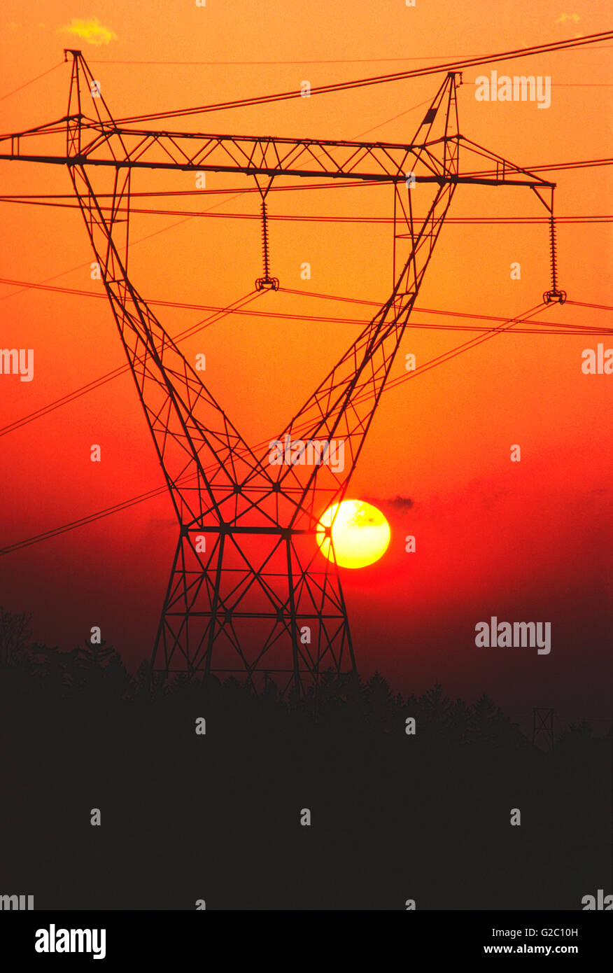 Sunset viewed through electrical transmission power lines and tower, upstate New York, USA - Stock Image