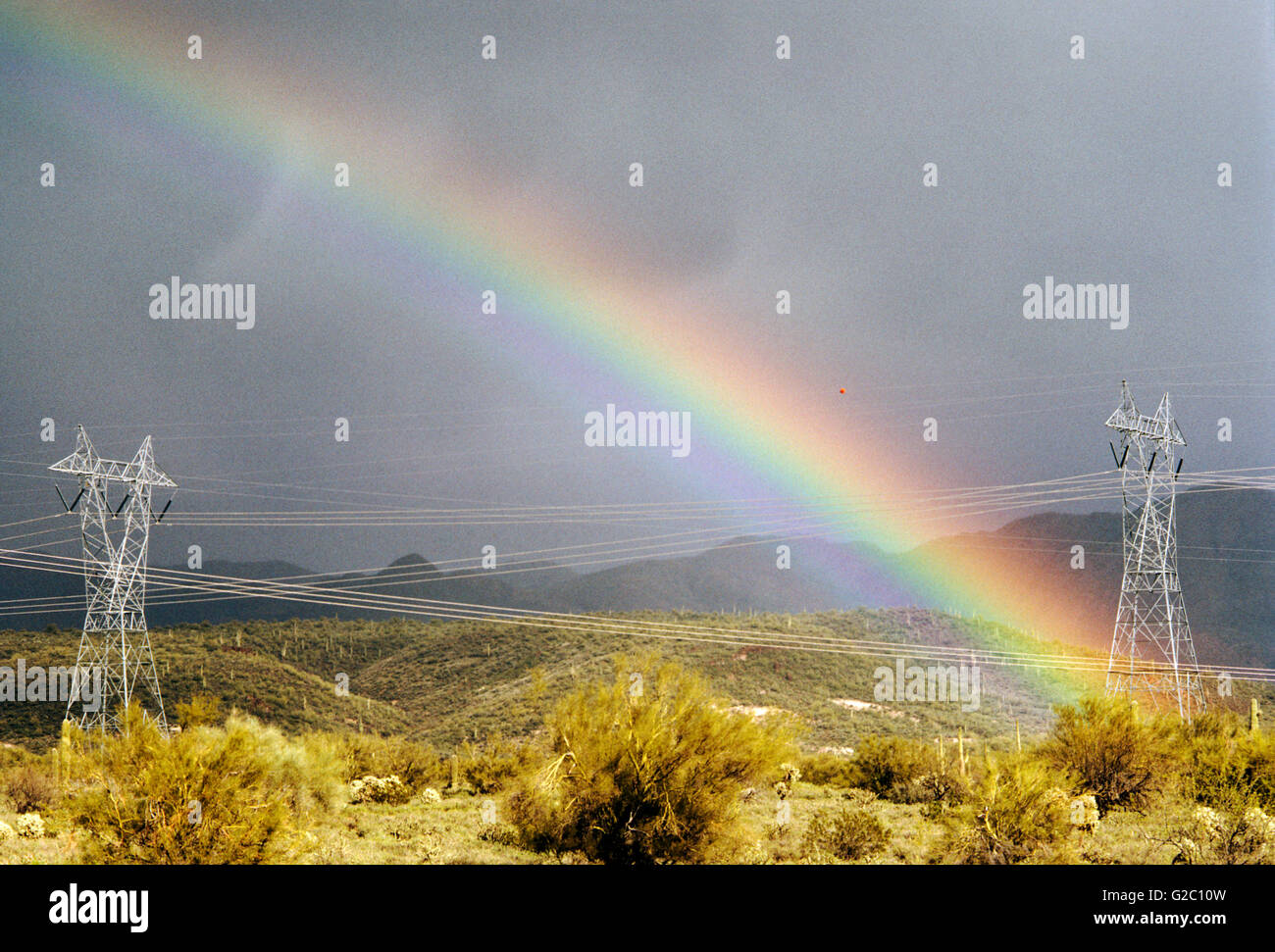 Electrical transmission lines and towers with a vivid, dramatic rainbow in the desert north of Phoenix, Arizona, - Stock Image