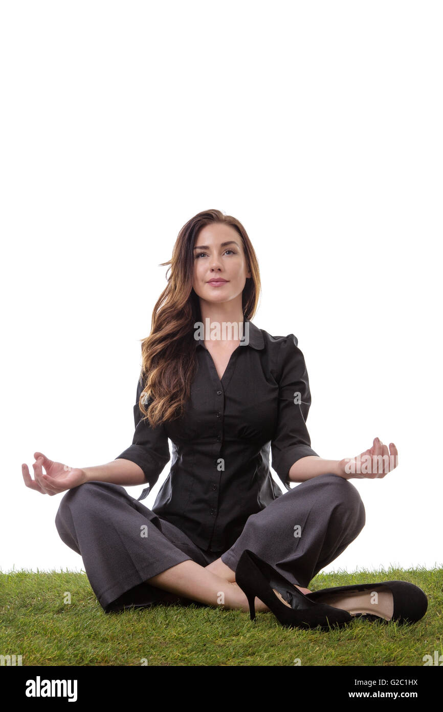 Pretty young business woman in a suit, sitting on grass in a crossed legs yoga pose, with her arms resting on her - Stock Image