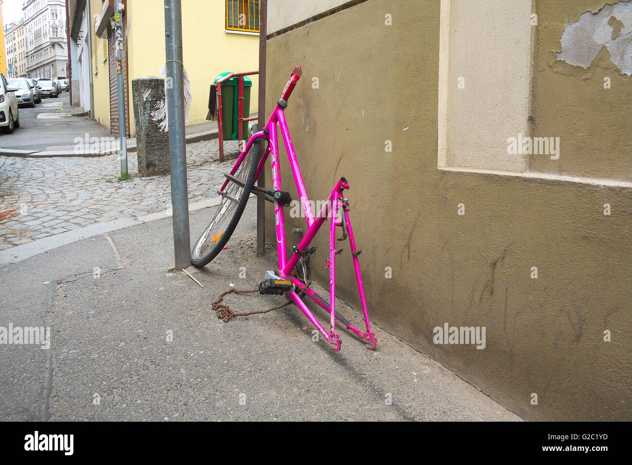 Broken and stolen beloved pink bicycle on the street. It looks like a corrupt petty street crime and violence. - Stock Image