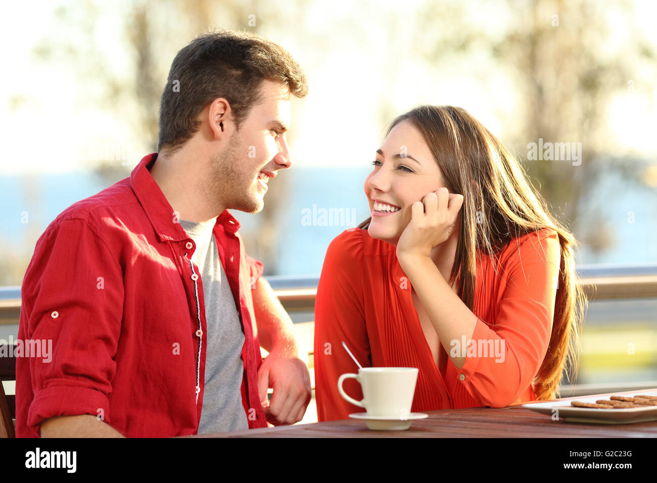 Candid couple date falling in love flirting in a terrace looking each other with tenderness thinking to kiss - Stock Image