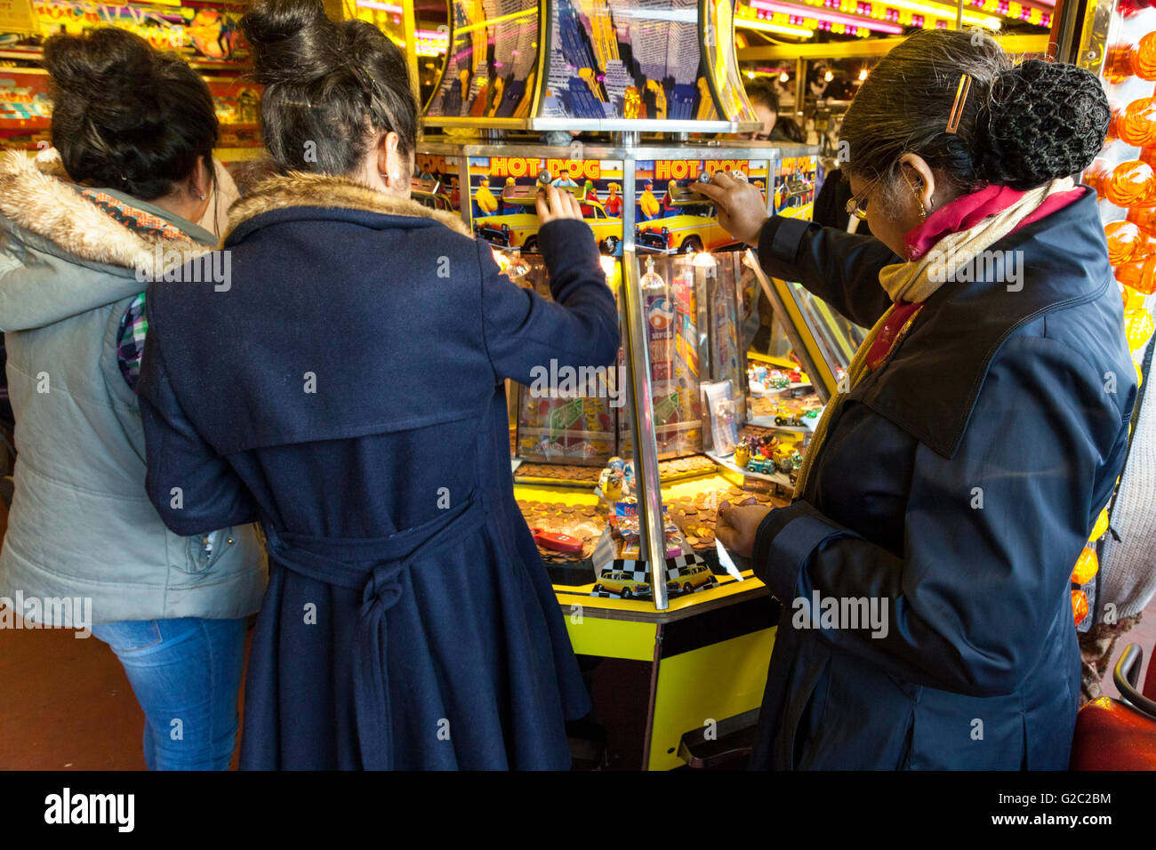 People playing a slot machine in an amusement arcade at Goose Fair, Nottingham, England, UK - Stock Image