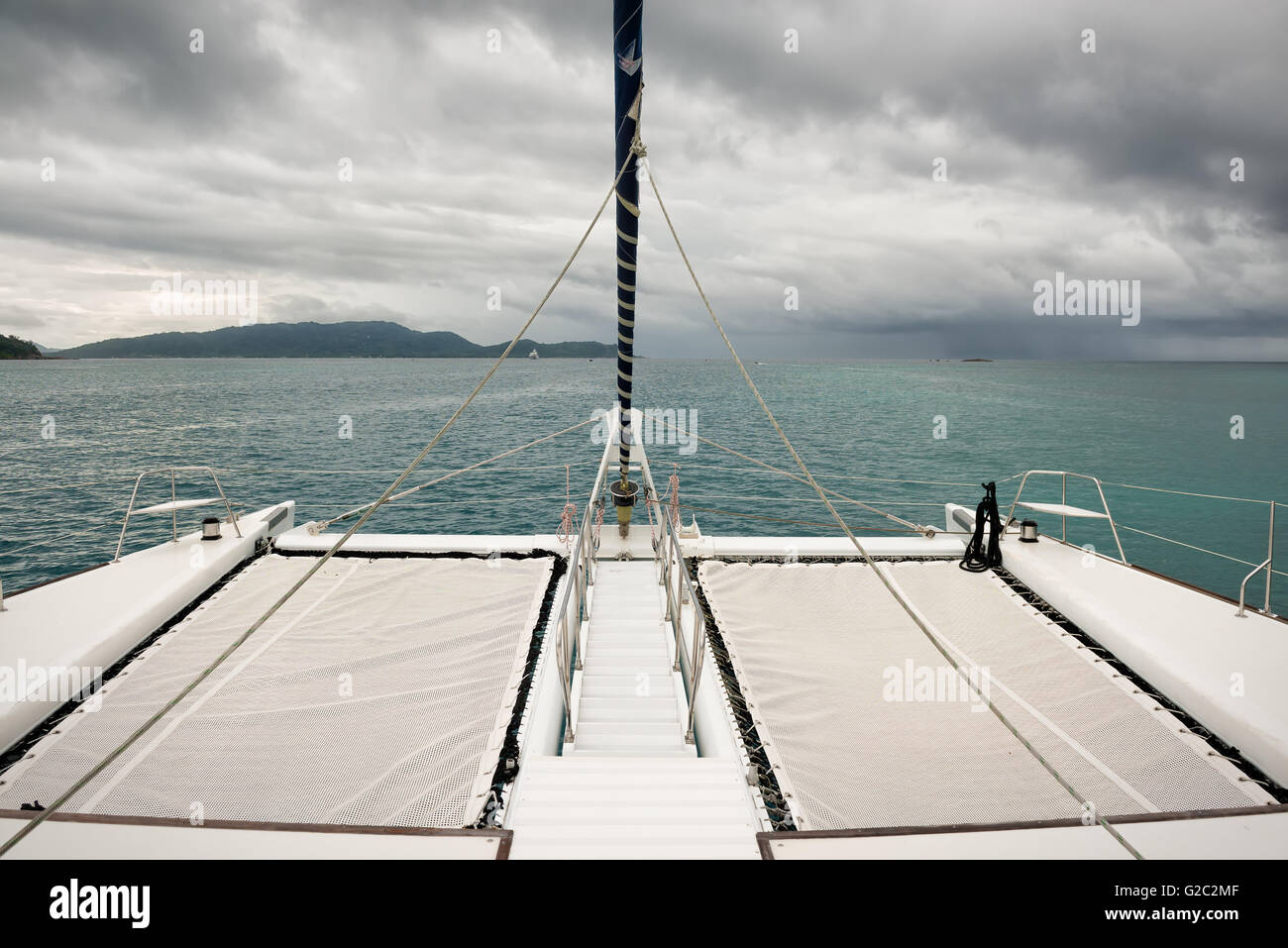 on board of a sailing catamaran towards the rain - Stock Image