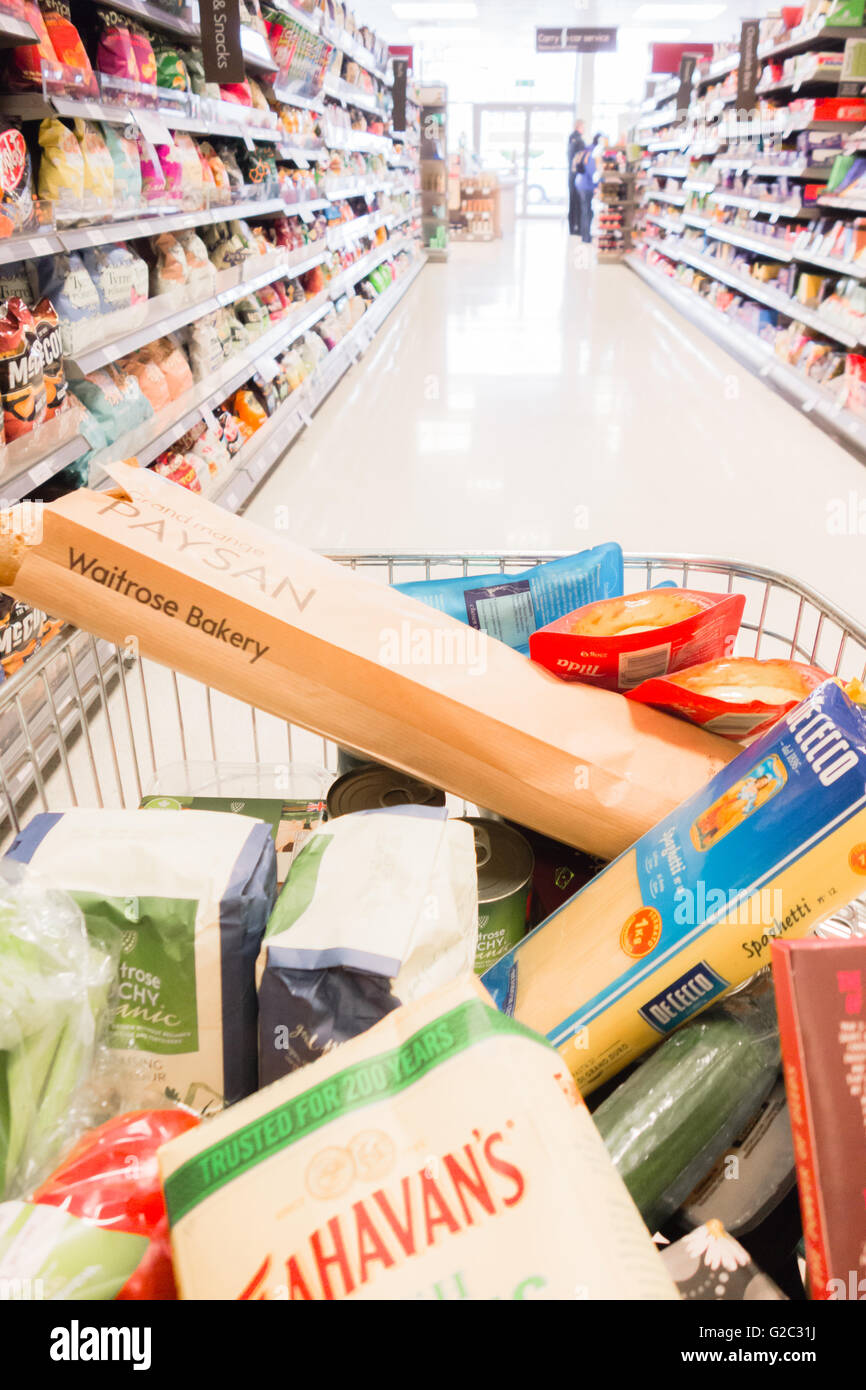 Waitrose shopping trolley full of groceries in shopping aisle - Stock Image