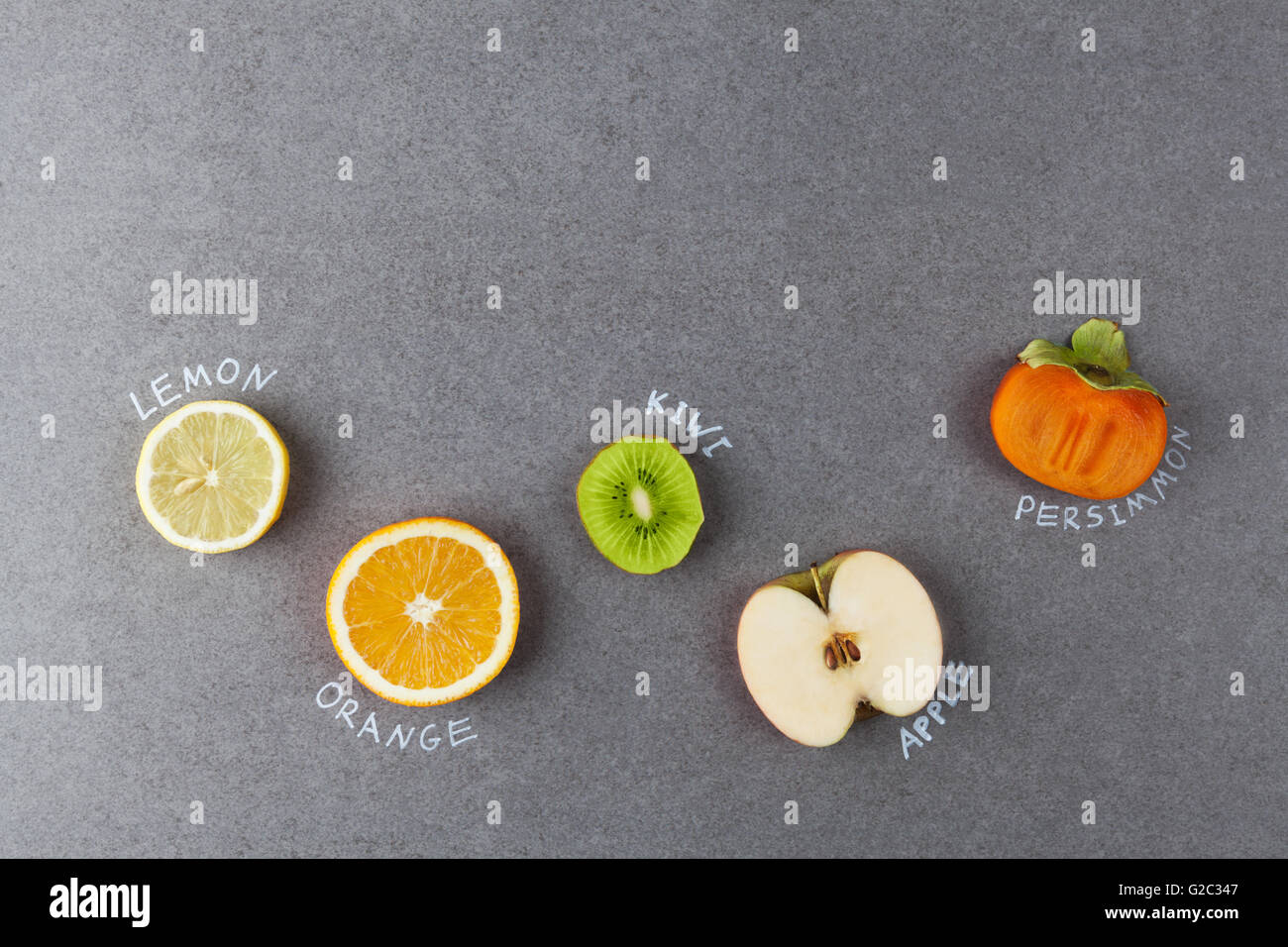 Slices of fruits with handwritten lables on stone surface. Lemon, orange, kiwi, apple, persimmon. Top view with - Stock Image