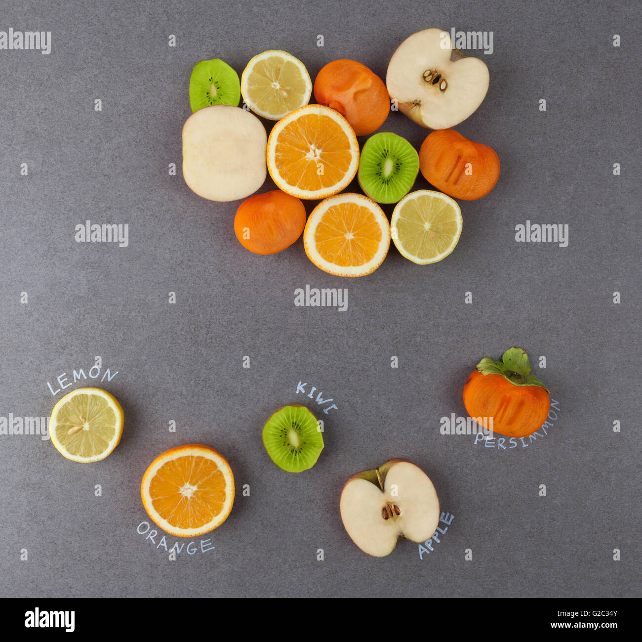 Slices of fruits with handwritten lables on stone surface. Lemon, orange, kiwi, apple, persimmon. Top view - Stock Image