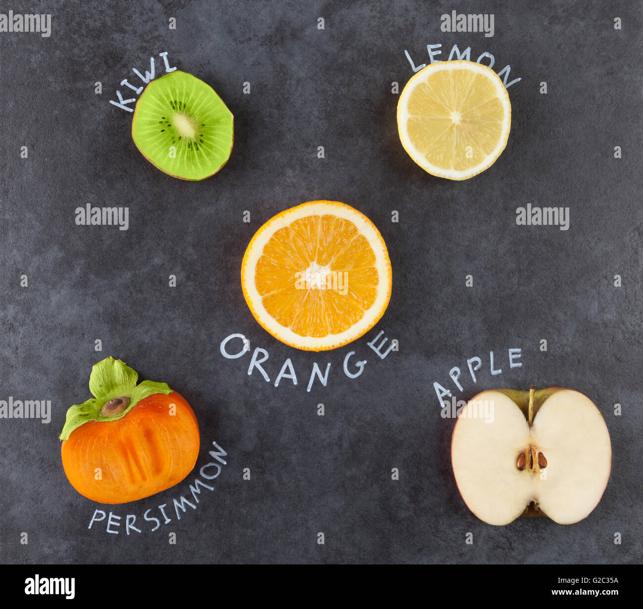 Slices of fruit on grungy dark background. Kiwi, lemon, orange, persimmon, apple. Top view. - Stock Image