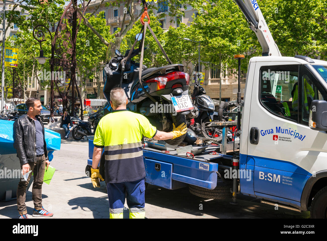Spain Catalonia Barcelona Eixample Passeig de Gracia parking fine penalty motor bike lifted tow away truck driver - Stock Image
