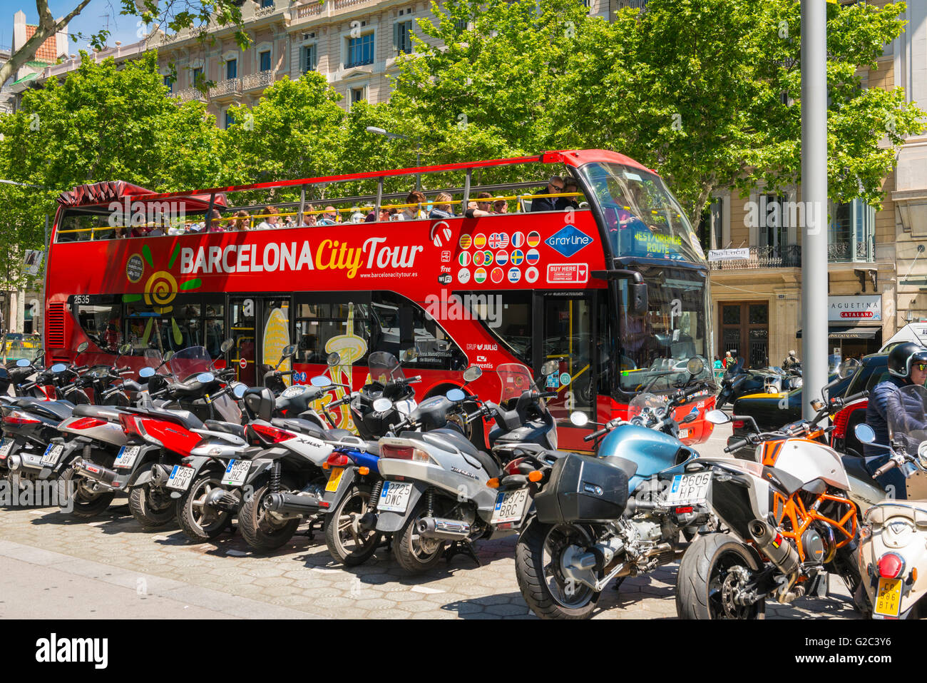 Spain Catalonia Barcelona Eixample Passeig de Gracia City Tourist Bus red double decker open top by motor bike cycle - Stock Image