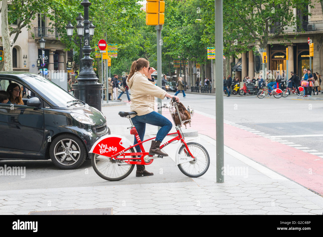 Spain Catalonia Barcelona young girl at lights on hire City bike bicycle cycle Viu BiCiNg Bicing red livery Stock Photo