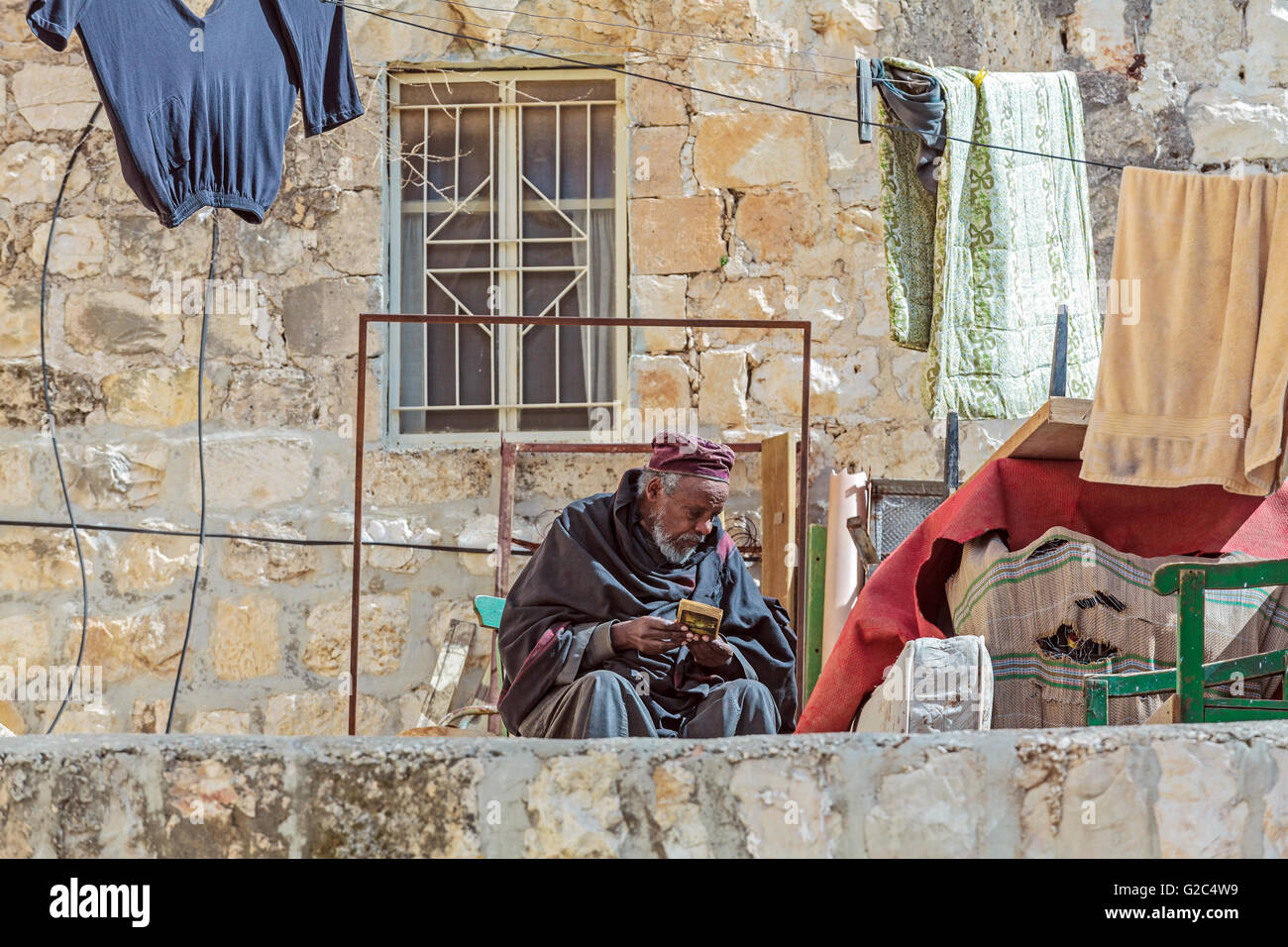JERUSALEM, ISRAEL - FEBRUARY 15, 2013: Priest of Ethiopian Orthodox Tewahedo Church sitting on balcony near Holy - Stock Image