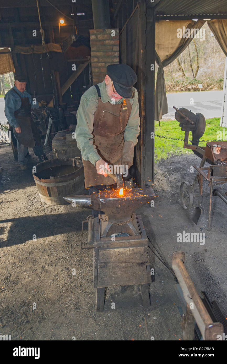 California, Coloma, Marshall Gold Discovery State Historic Park, blacksmith hammering hot metal on anvil - Stock Image