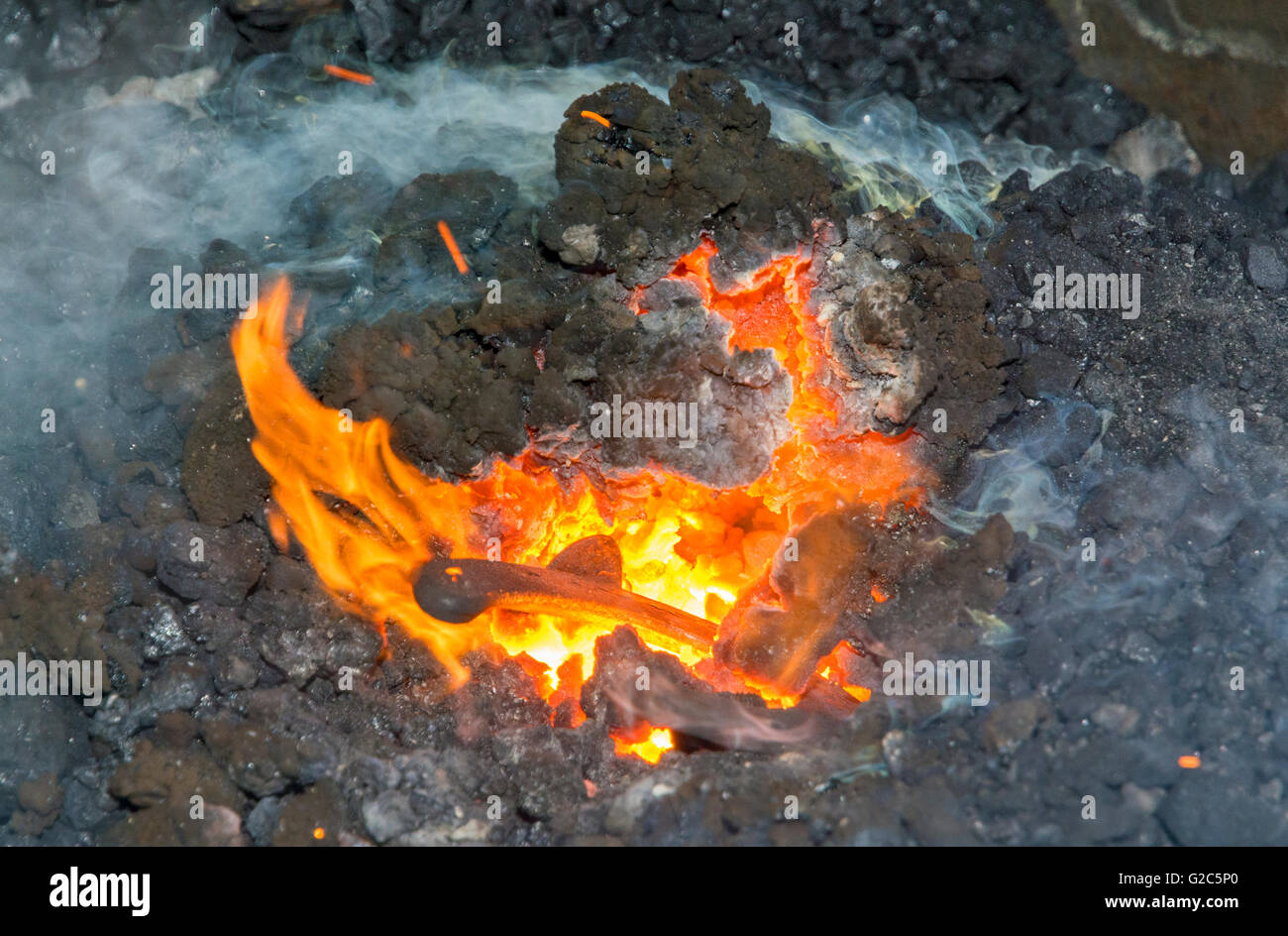 California, Coloma, Marshall Gold Discovery State Historic Park, blacksmith, red hot horseshoe heated in forge - Stock Image