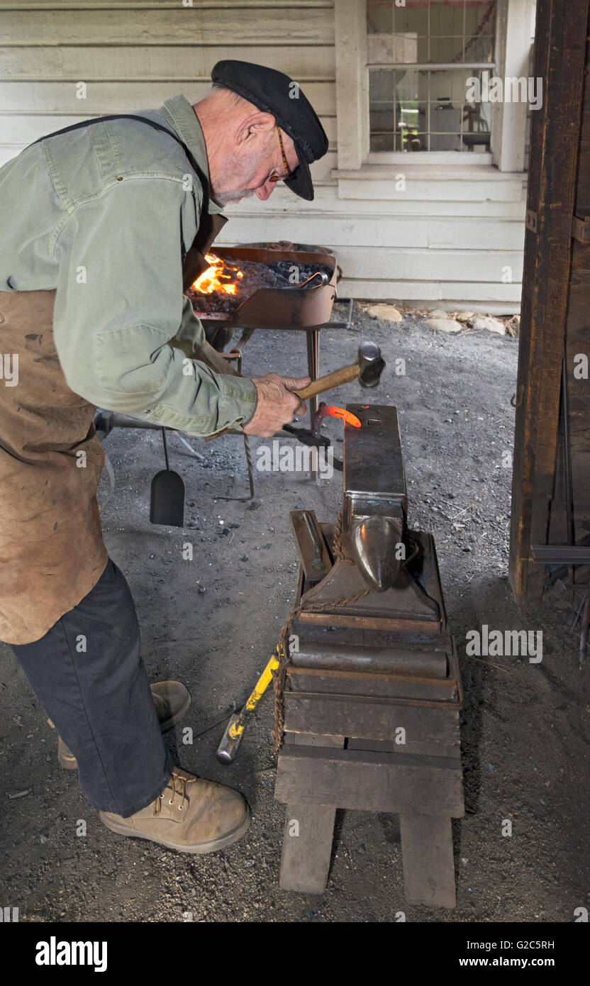California, Coloma, Marshall Gold Discovery State Historic Park, blacksmith hammering red hot horseshoe on anvil - Stock Image
