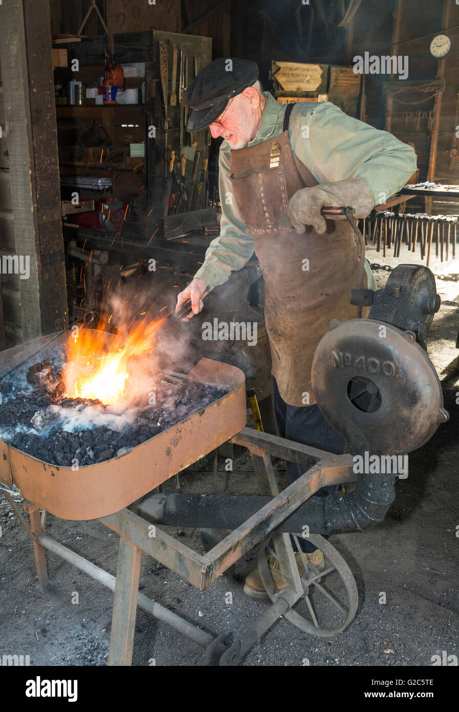 California, Coloma, Marshall Gold Discovery State Historic Park, blacksmith heating metal in forge - Stock Image