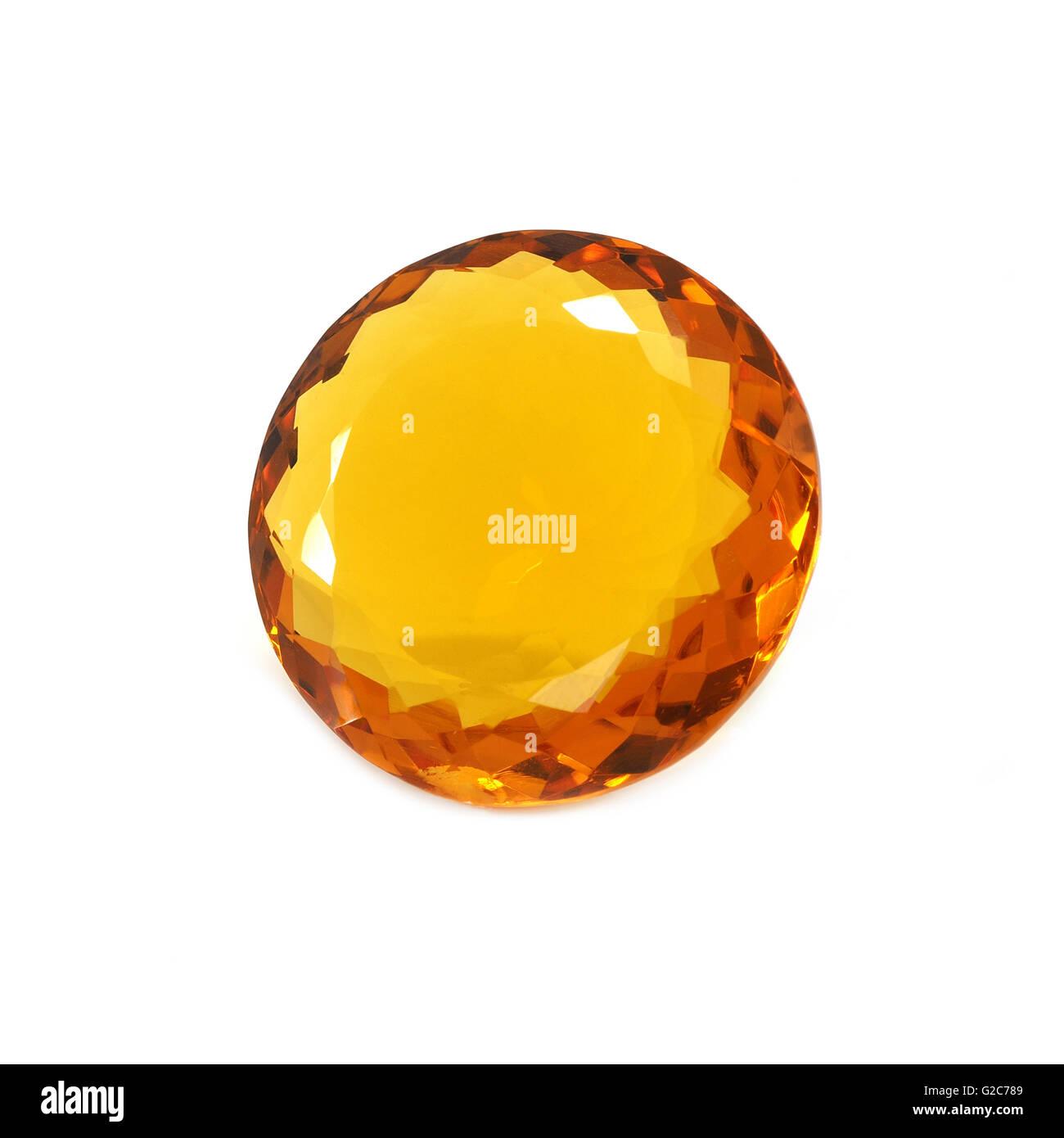 Round shaped orange gemstone on a white background. - Stock Image
