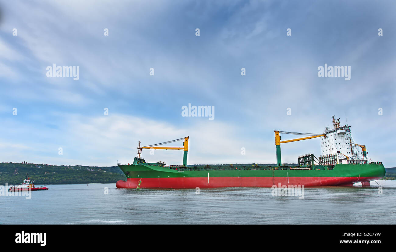 Tugboats assisting container cargo ship to harbor. - Stock Image