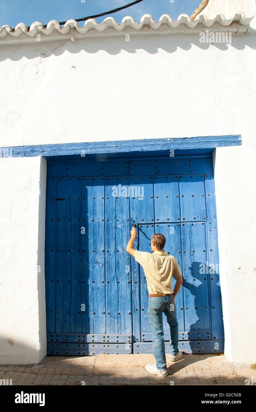 Man knocking at wooden door. Almagro, Ciudad Real province, Castilla La Mancha, Spain. - Stock Image