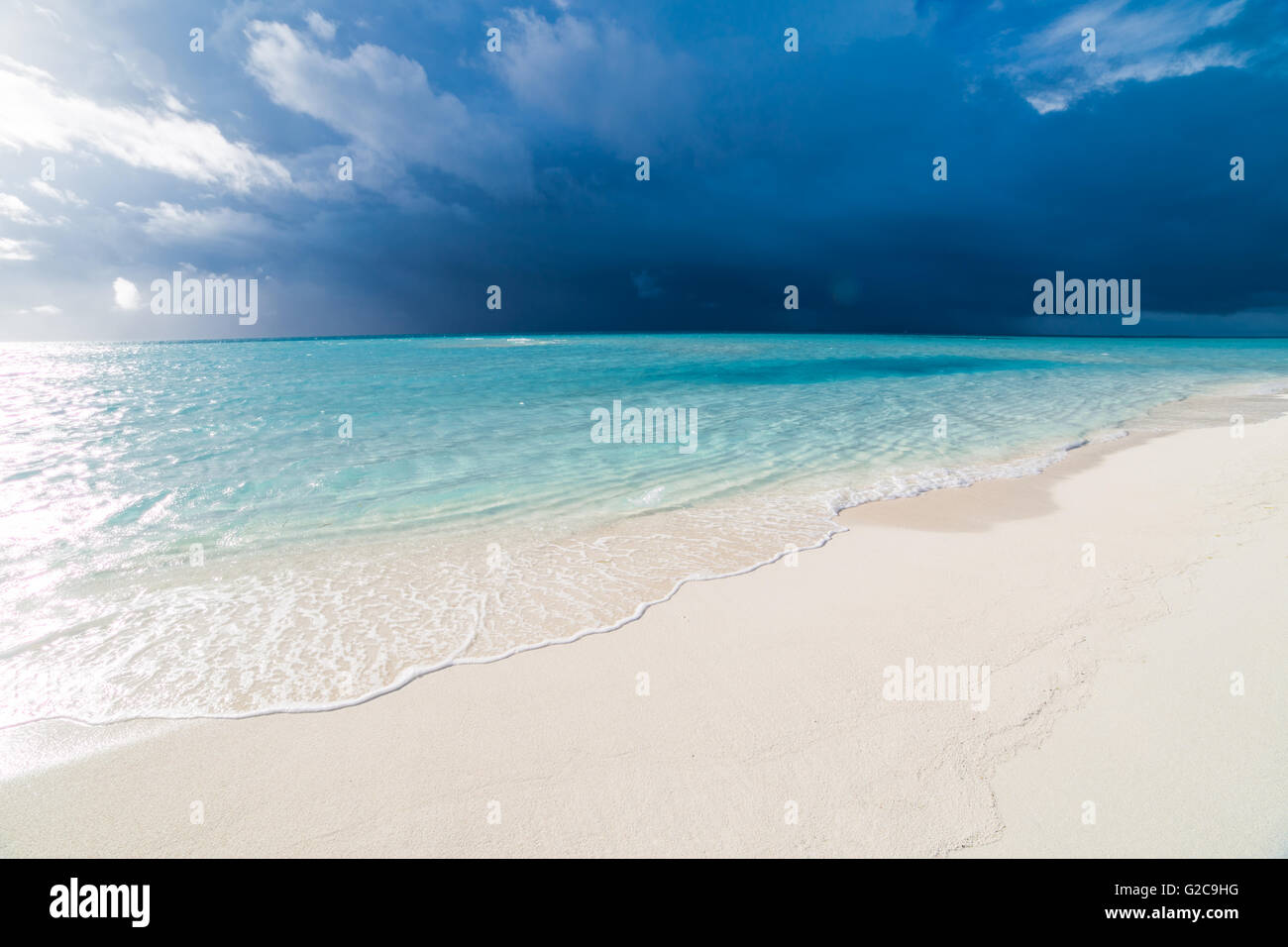 White tropical beach in Maldives with blue lagoon and a tropical storm - Stock Image