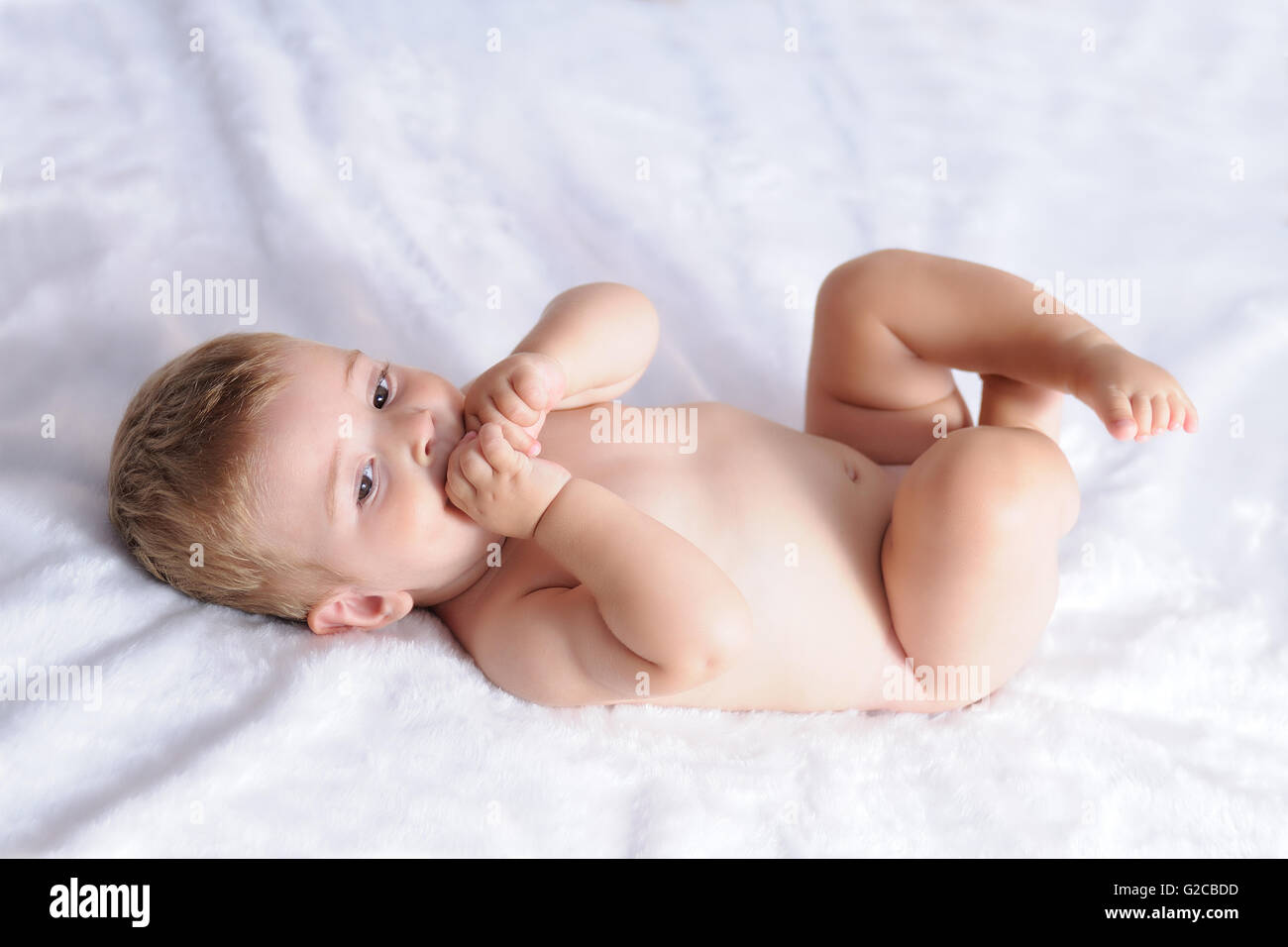 baby biting hands lying on a blanket of white hair - Stock Image
