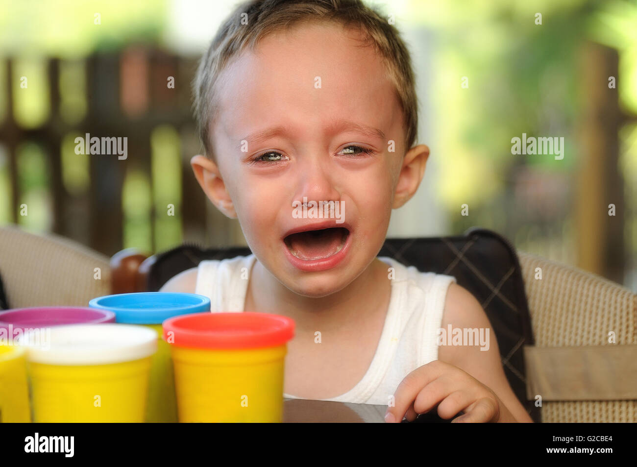 child crying on the terrace of a summer school - Stock Image