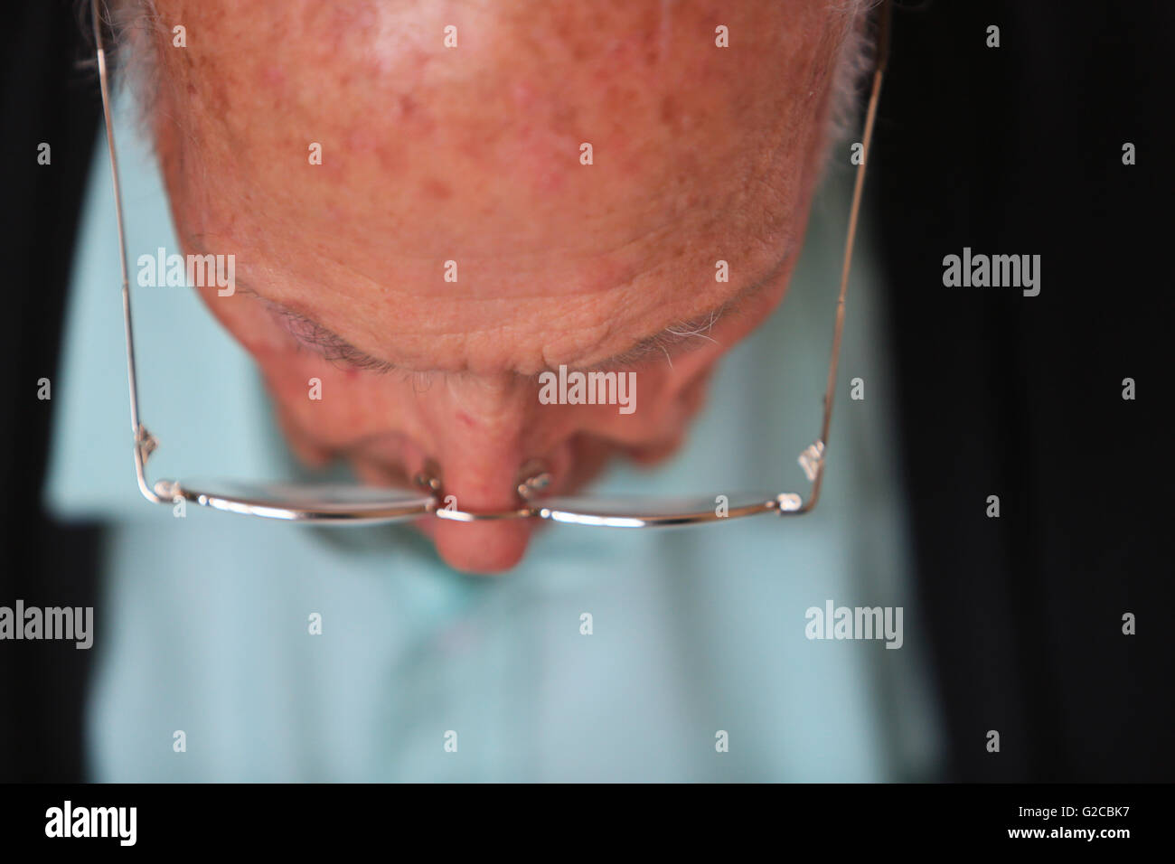 A man in his 80's wearing glasses looking downwards reading - Stock Image
