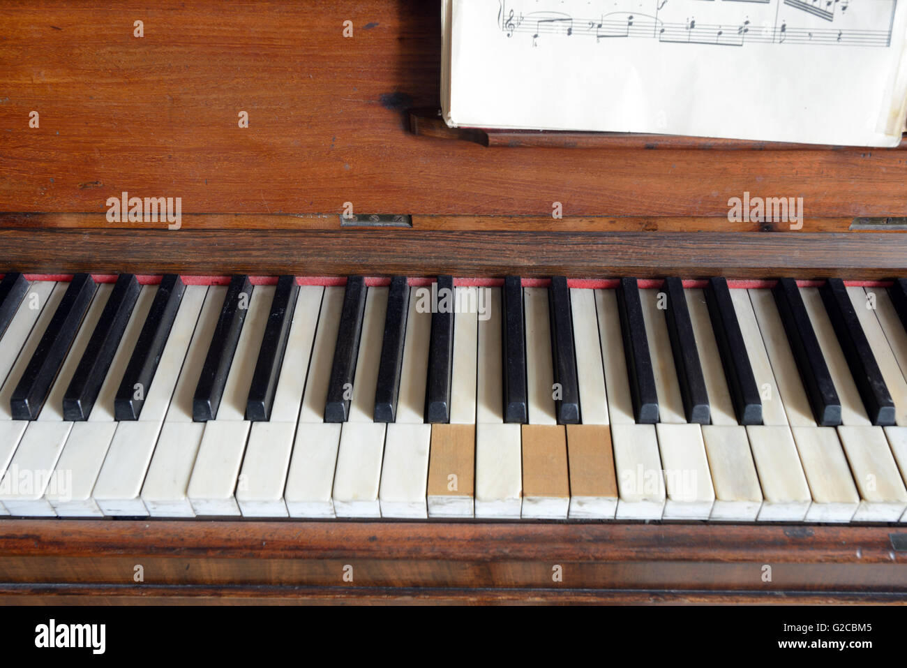 Old Piano with Missing Keys and Sheet Music or Score - Stock Image
