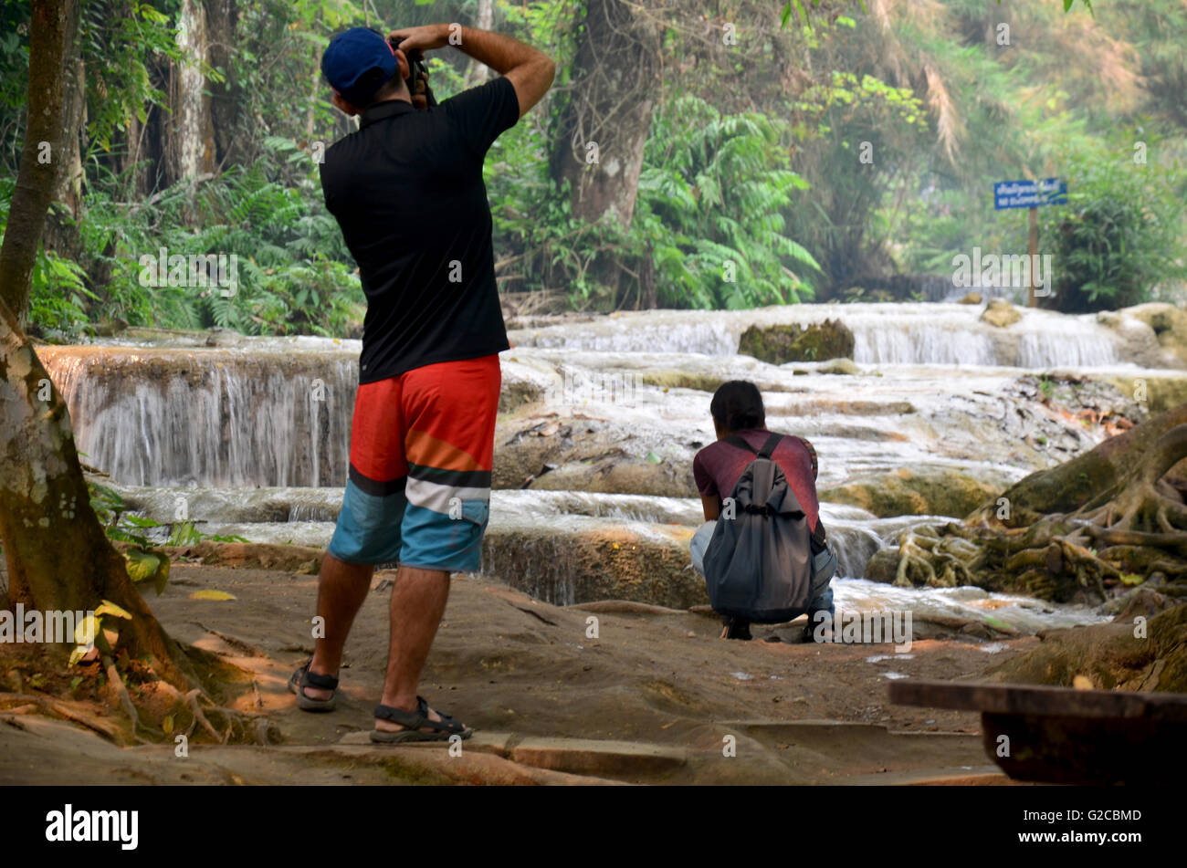 Traveller people travel and take photo with view of Kuang Si Falls or Tat Kuang Si Waterfalls on April 8, 2016 in - Stock Image