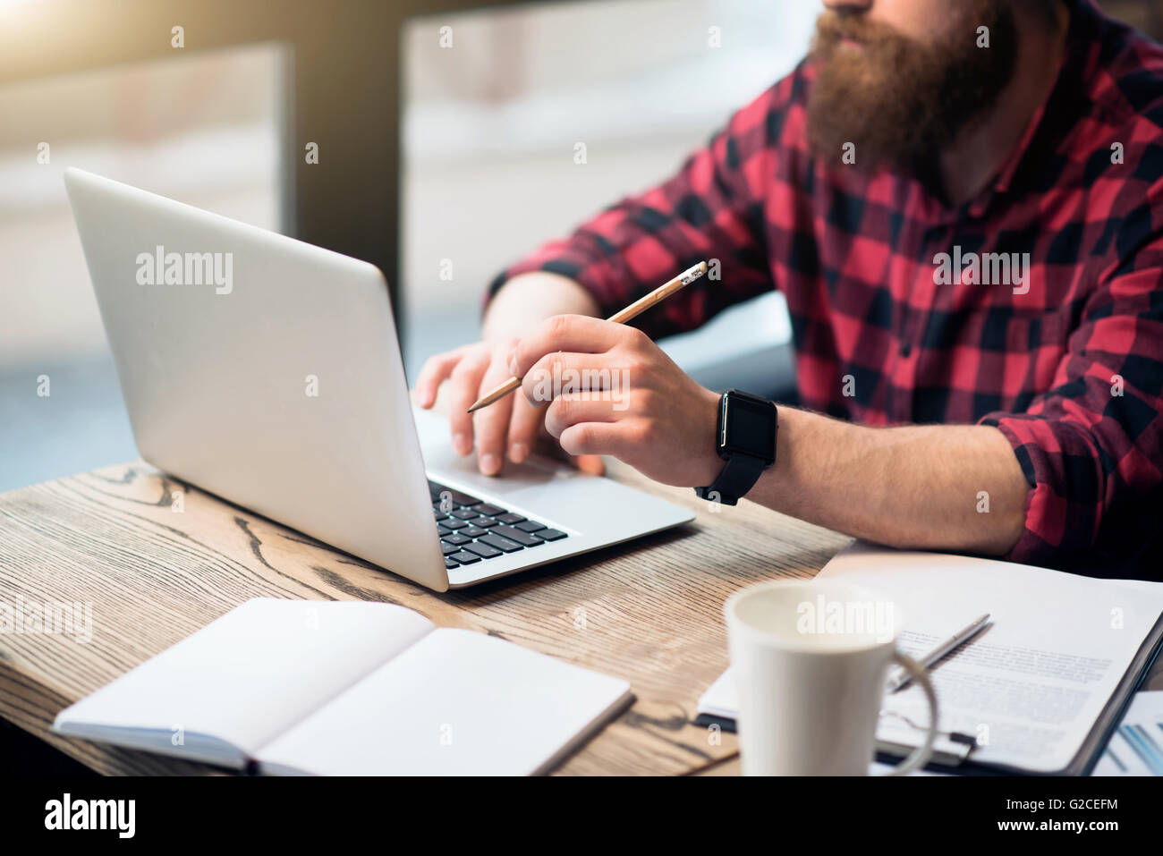 Brutal bearded man sitting at the table - Stock Image