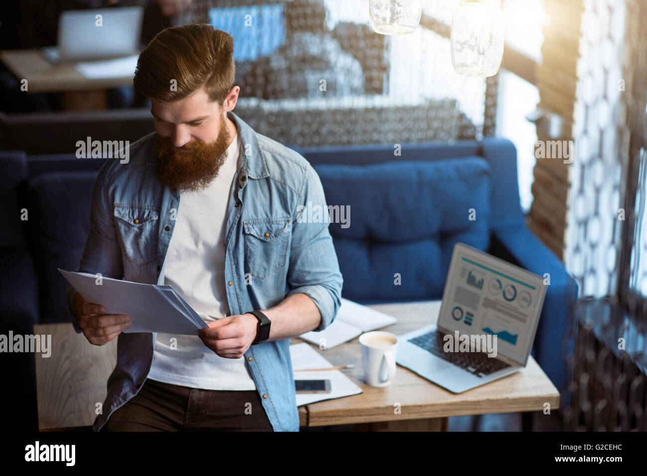 Positive  bearded man standing in the office - Stock Image