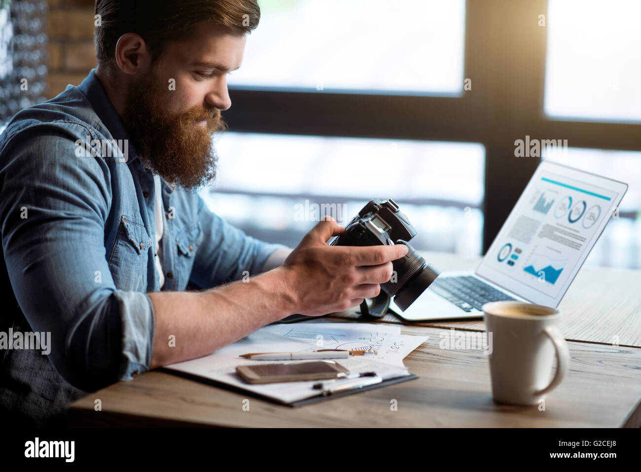 Glad  bearded man sitting at the table - Stock Image