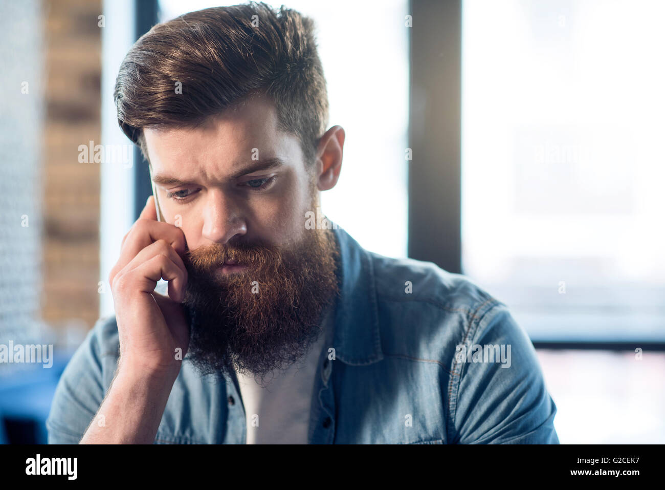Pleasant bearded man using cell phone - Stock Image