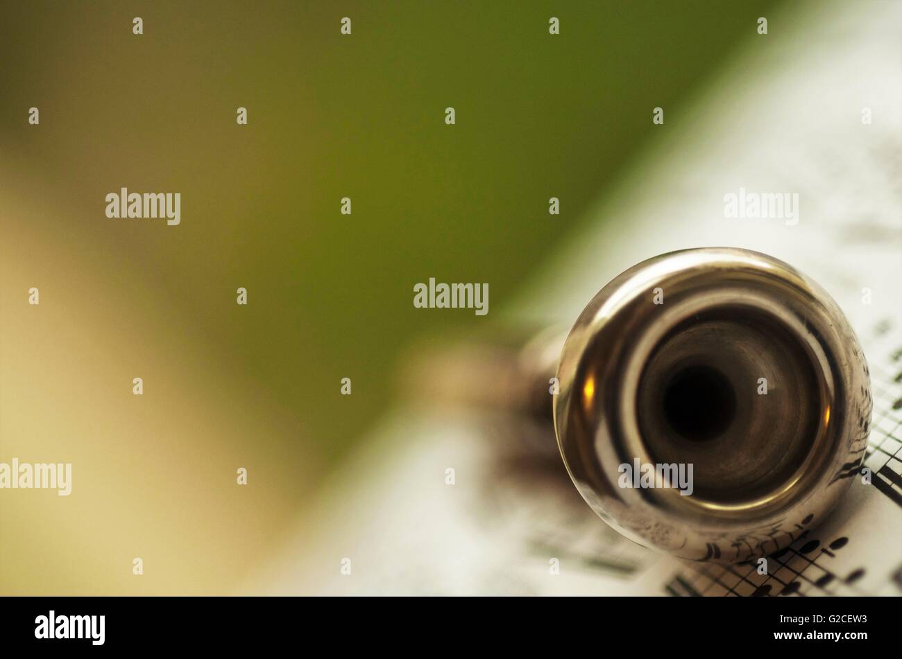 trumpet mouthpiece posed on a book of music sheets - Stock Image