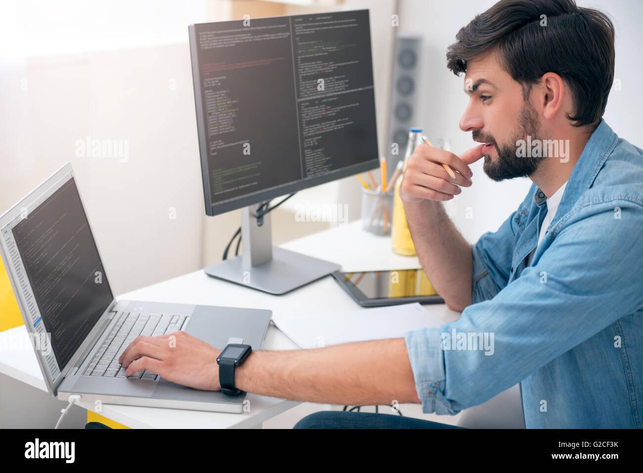 Man working on his laptop - Stock Image