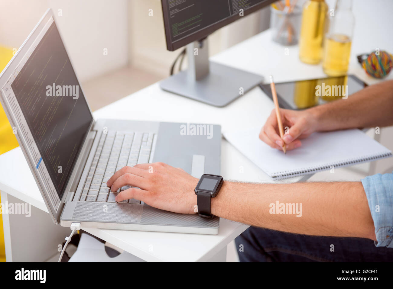 Hands of man tapping on the laptop - Stock Image