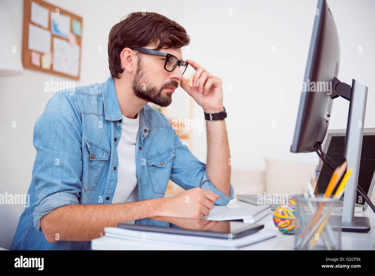 Man looking at screen of computer - Stock Image
