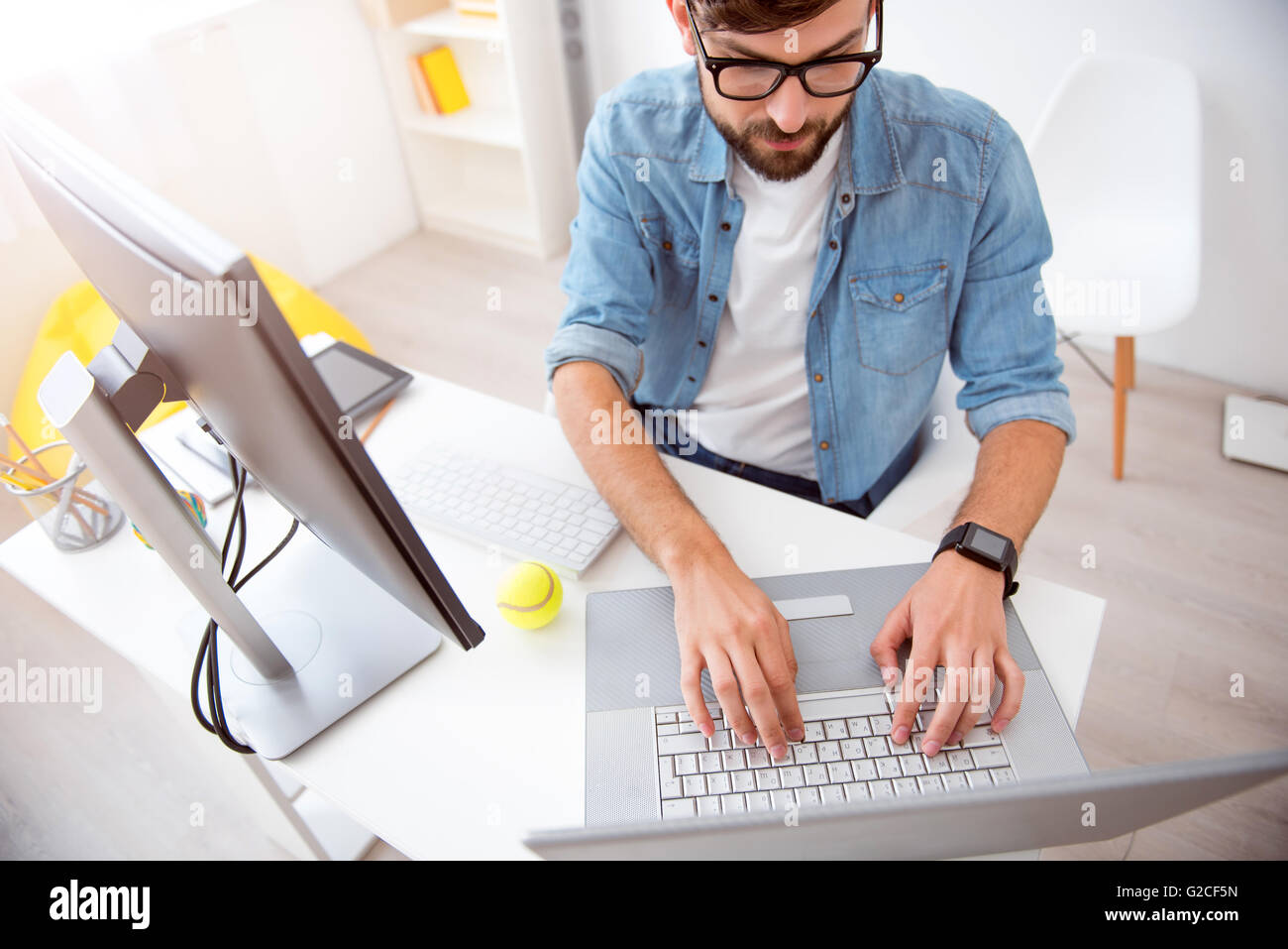 Guy tapping on his laptop - Stock Image