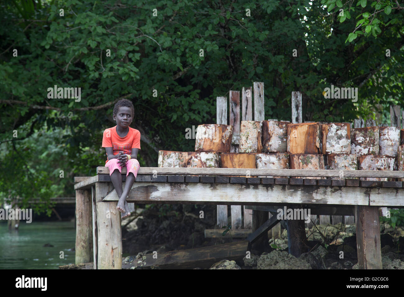Seghe, Solomon Islands - June 16, 2015: Local boy sitting on a pier - Stock Image