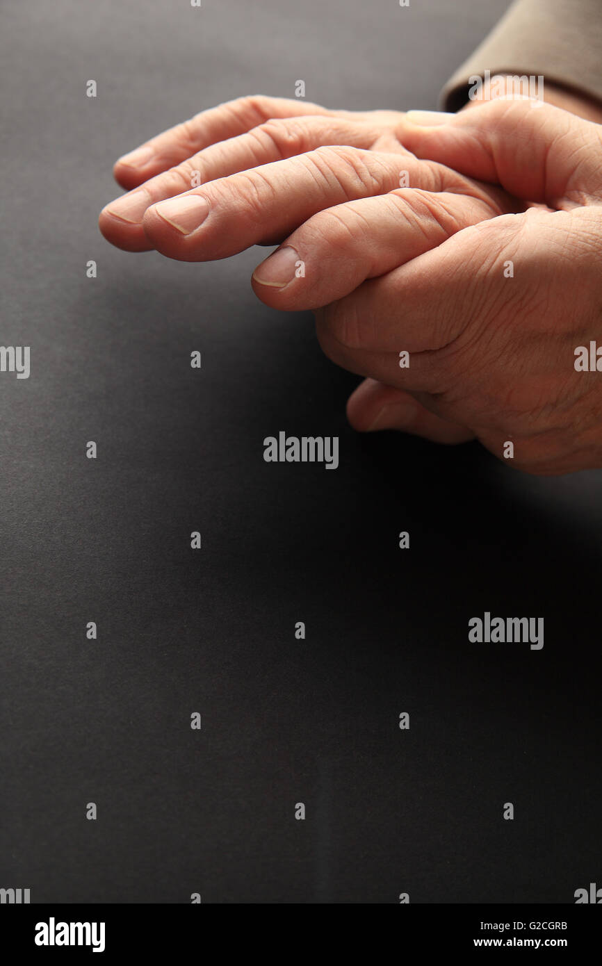 A man grips his aching hand on a dark background with copy space. - Stock Image