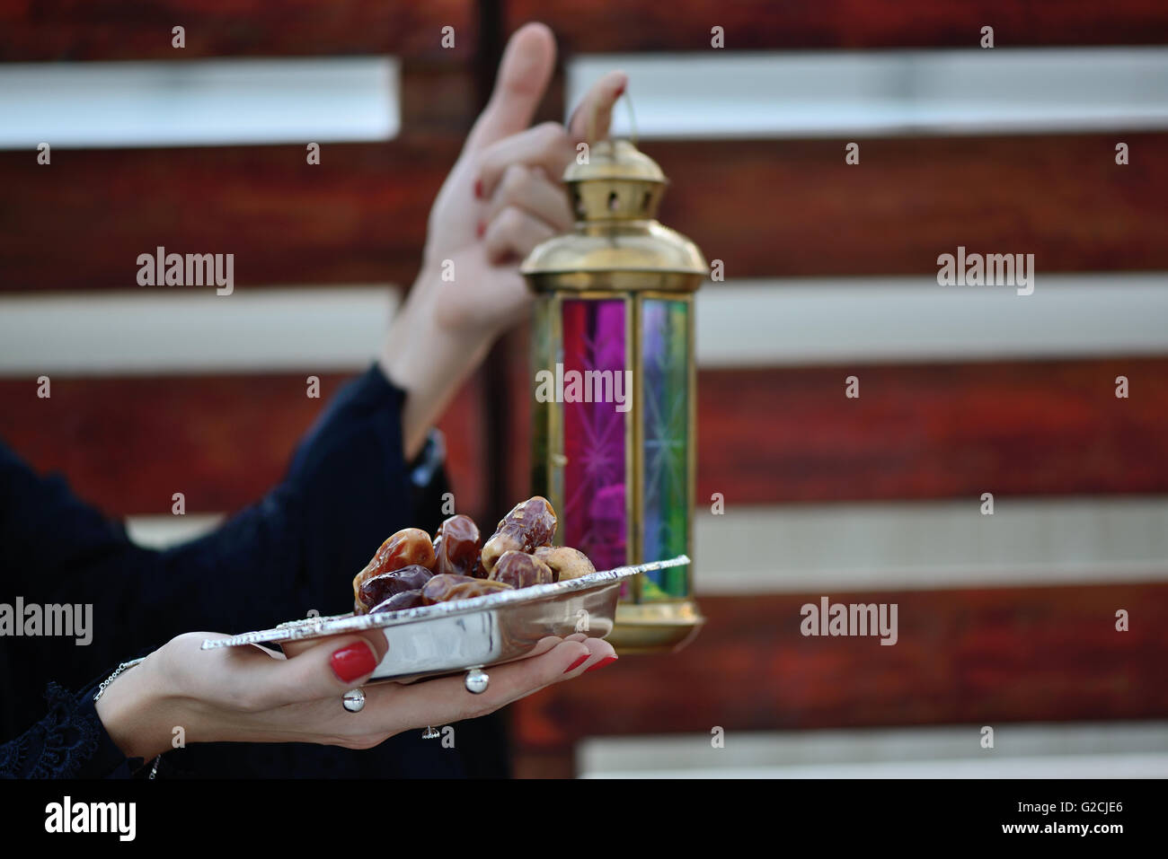 Emarati Arab woman holding dates plate and Ramadan Lamp, Dubai, United Arab Emirates. - Stock Image