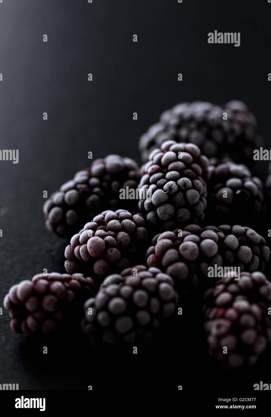 blackberries frozen on a black stone, macro photo showing a beautiful ice texture Stock Photo